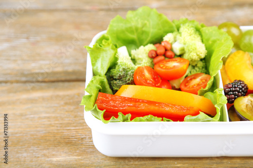canvas print picture Tasty vegetarian food in plastic box on wooden table