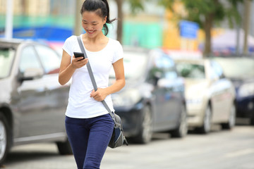 young woman use her cell phone walking on parking lot