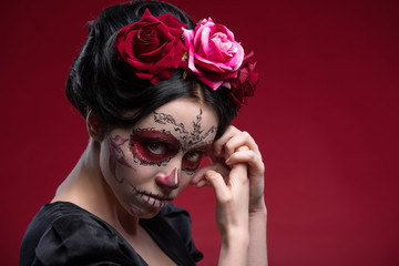 Portrait of young girl in black dress with Calaveras makeup and