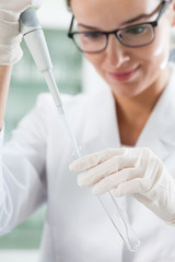 Lab technician using pipette