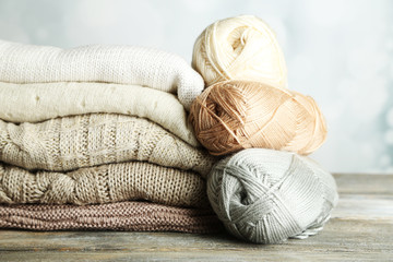 Knitting clothes and yarn on light background