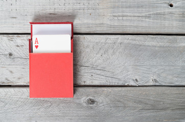 Playing cards in a red box on wooden background