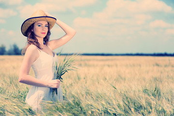 Beautiful young woman with ears in field