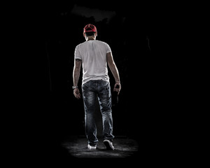 Boy Walking away , see from behind , handgun and cap