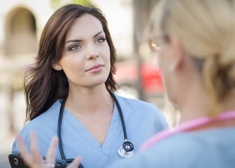 Two Young Adult Female Doctors or Nurses Talking Outside