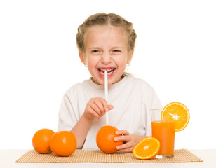 little girl with oranges drink juice with a straw