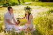 Young beautiful couple relaxing on the meadow with dandelions