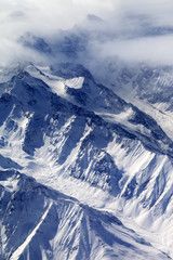 Top view on snow mountains and glacier in fog