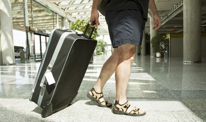 Man with suitcase at airport terminal