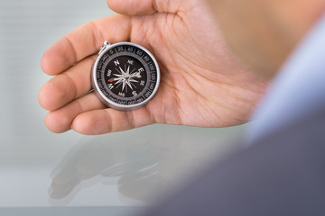 Business advisor holding compass