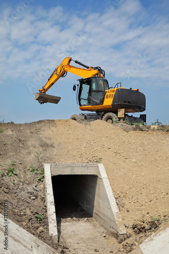 Agriculture, irrigation channel construction site in field - 71390376