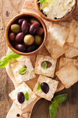 crackers with soft cheese and olives. healthy appetizer