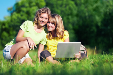 Two happy girl with laptop in summer park