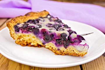 Pie with blueberries and spoon in plate on board