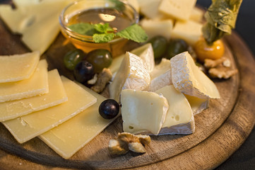 Wooden plate with cheese in assortment