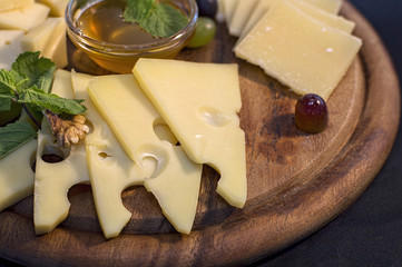 Cheese set on wooden plate with honey, nuts and herbs
