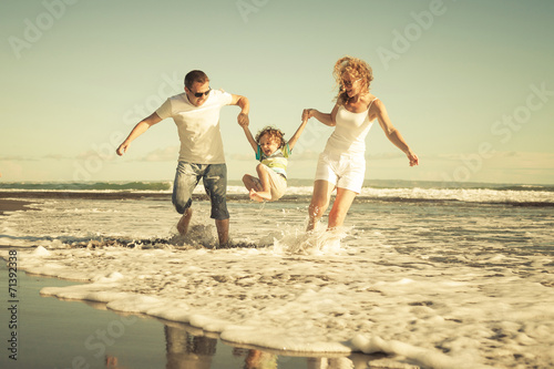 Happy family playing on the beach at the day time poster