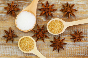 White and brown sugar on wooden spoons and star anise