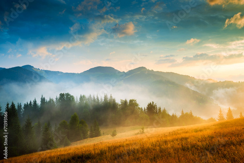 Foto Spatwand Europa Amazing mountain landscape with fog and a haystack