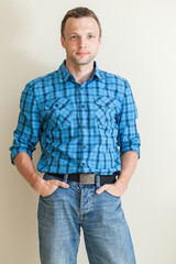 Young Caucasian man in blue checkered shirt and jeans