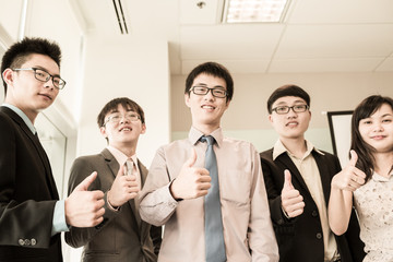 Business team holding their thumbs up
