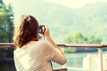 young female enjoying boat ride, taking photos, UK