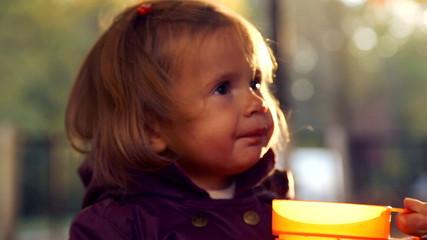 Child drinks tea in autumn park.