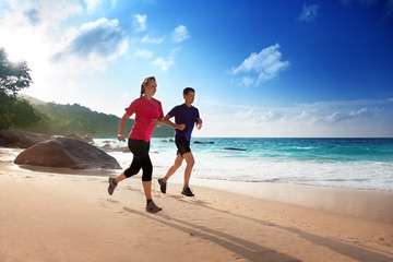 Man and woman running on tropical beach at sunset
