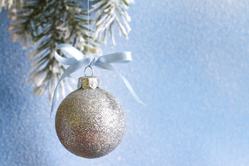 Christmas ball on fir branches and snowy blue background