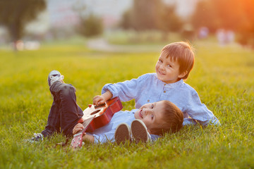 Two adorable boys, sitting on the grass, playing guitar