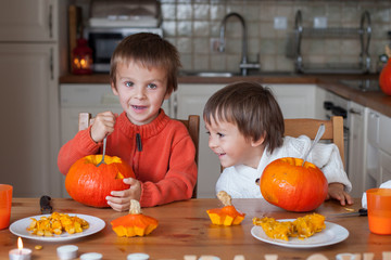 Two adorable boys, preparing jack o lantern for Halloween