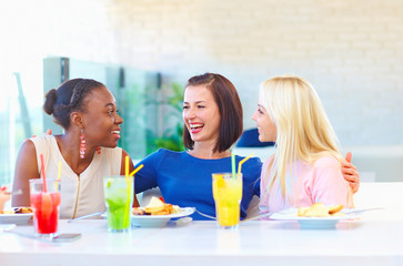 multiracial female friends enjoing meal in restaurant