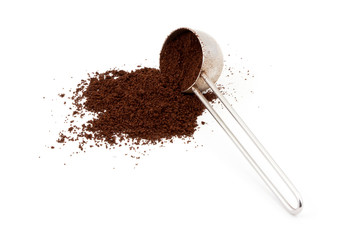 A pile of ground coffee and a spoon isolated on white