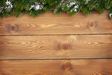 Christmas fir tree with snow on rustic wooden board