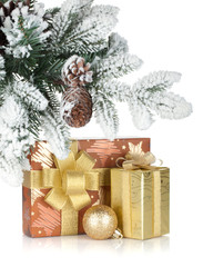 Gift box and christmas decor under snowy fir tree
