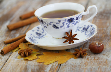 Cup of tea, star anise, cinnamon, autumn leaves and chestnuts