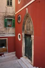 Church door on a red facade on the streets of Sibenik, Croatia.