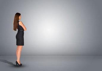 Businesswoman standing in an empty gray room. Rear view