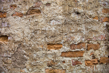 Partly plastered brick wall with rich texture
