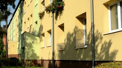 building (house) - flats - exterior - sun rays - flowers