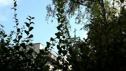 nature (trees) - modern church (tower with a crucifix)
