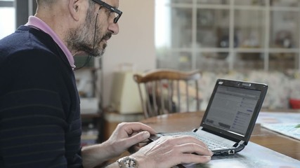 elderly man using laptop at home