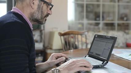 elderly man using laptop at home