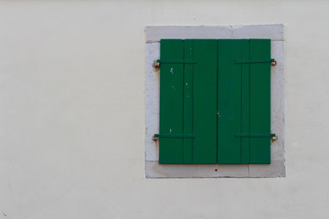 Window closed green shutters on the wall