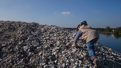 Junge klettert auf steinen bei see