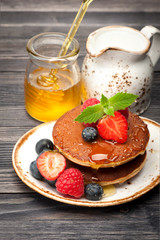 Delicious pancakes with honey and berries