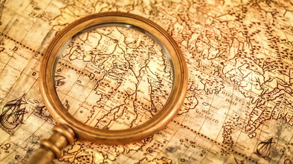 Vintage still life. Vintage magnifying glass lies on ancient map