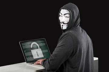 Anonymous Hacker in front of a security laptop isolated on black