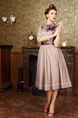 Pin Up beautiful woman in vintage interior by the fireplace