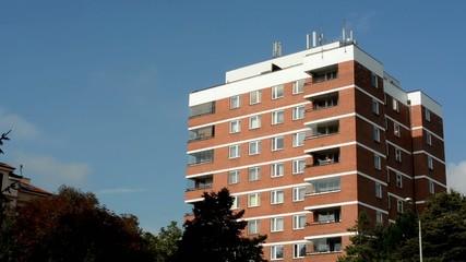modern building - balcony - windows - blue sky - trees